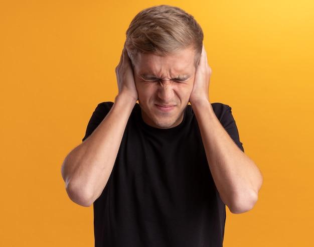 Insoddisfatto con gli occhi chiusi giovane bel ragazzo che indossa la camicia nera che mette le mani sulle orecchie isolate sul muro giallo