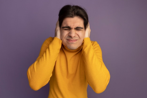 Недовольный закрытыми глазами молодой красивый парень в желтом свитере с высоким воротом, положив руки на уши, изолирован на фиолетовой стене