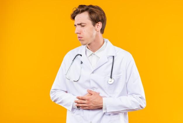 Scontento con gli occhi chiusi giovane medico maschio che indossa abito medico con stetoscopio afferrò lo stomaco dolorante isolato sulla parete arancione