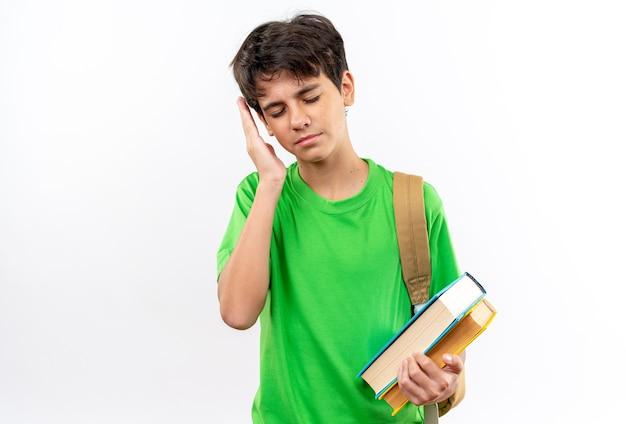 Scontento con gli occhi chiusi giovane scolaro che indossa uno zaino con in mano libri