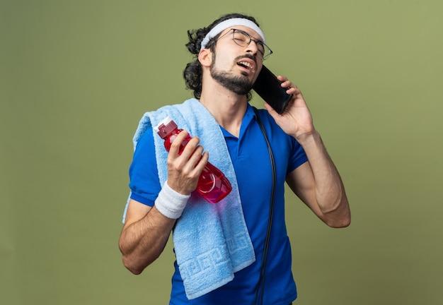Dispiaciuto con gli occhi chiusi, il giovane sportivo che indossa la fascia con il braccialetto e l'asciugamano sulla spalla parla al telefono tenendo una bottiglia d'acqua