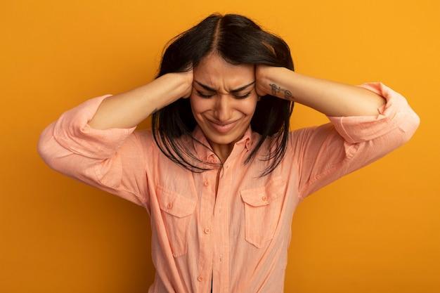 노란색 벽에 고립 된 사원에 손을 댔을 분홍색 티셔츠를 입고 낮춘 머리 젊은 아름다운 소녀 불만