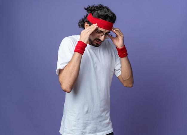 Недовольный опущенной головой молодой спортивный мужчина в повязке на голову с браслетом, положив руки на висок