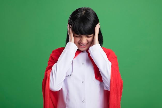 Insoddisfatto con la testa abbassata giovane ragazza del supereroe che indossa uno stetoscopio con veste medica e mantello che mette le mani sulle orecchie isolate su verde