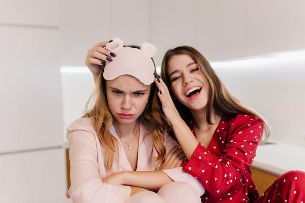 Donna dispiaciuta in maschera rosa in posa con le braccia conserte in cucina. foto dell'interno della ragazza bianca che ride in pigiama rosso che ride mattina.