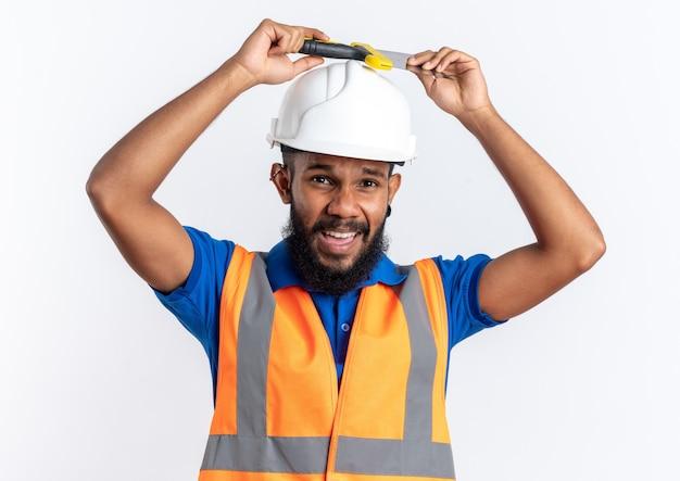 복사 공간 흰색 배경에 고립 된 그의 머리 위에 스크레이퍼를 들고 안전 헬멧 제복을 입은 불쾌한 젊은 아프리카 계 미국인 작성기 남자