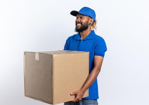 Недовольный молодой афро-американский курьер, держащий большую картонную коробку на белом фоне с копией пространства