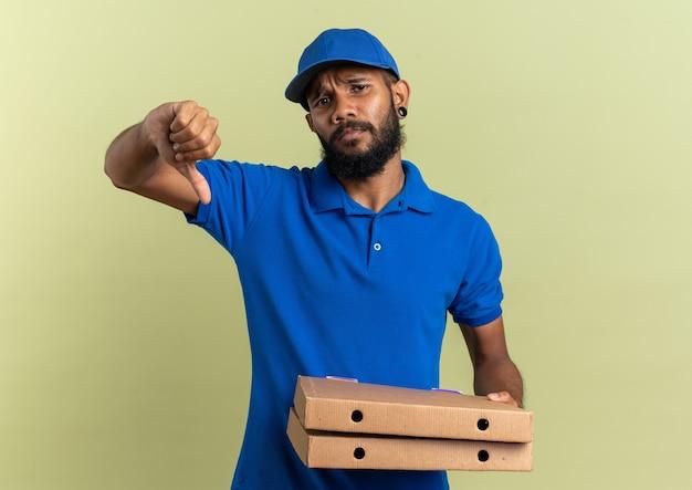 Недовольный молодой афро-американский курьер, держащий коробки для пиццы и листающий вниз, изолирован на оливково-зеленом фоне с копией пространства