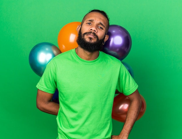 Недовольный молодой афро-американский парень в зеленой футболке стоит перед воздушными шарами, положив руку на бедро, изолированную на зеленой стене