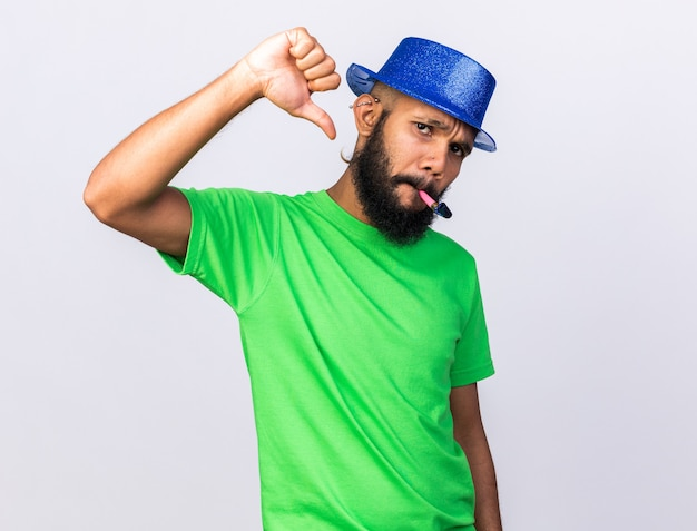 Unpleased young afro-american guy wearing party hat blowing party whistle showing thumb down