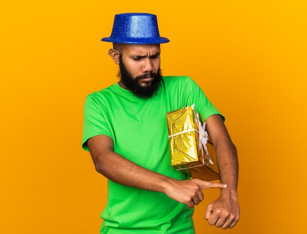 손목 시계를 보여주는 선물 상자를 들고 파티 모자를 쓰고 불쾌한 젊은 아프리카계 미국인 남자