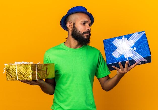 オレンジ色の壁に隔離されたギフトボックスを保持しているパーティーハットを身に着けている不機嫌な若いアフリカ系アメリカ人の男