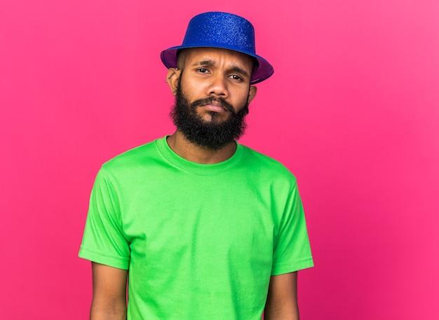ピンクの壁に隔離されたパーティーハットを身に着けている不機嫌な若いアフリカ系アメリカ人の男