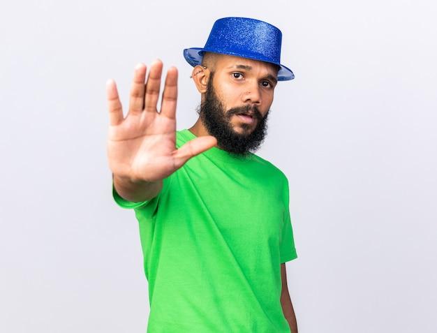 Giovane ragazzo afroamericano scontento che indossa un cappello da festa che mostra il gesto di arresto isolato sul muro bianco