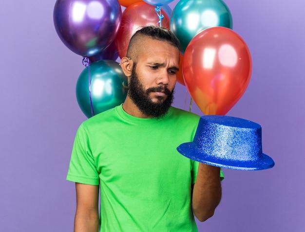 気球の前に立っているパーティーハットをかぶっている不機嫌な若いアフリカ系アメリカ人の男