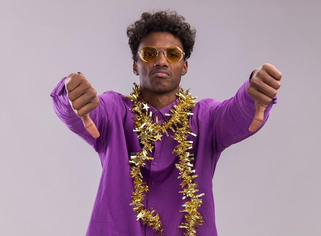 Unpleased young afro-american man wearing glasses with tinsel garland around neck looking at camera showing thumbs down isolated on white background