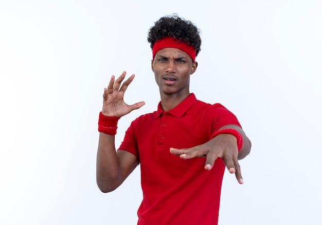 Il giovane sportivo afroamericano dispiaciuto che indossa la fascia e il braccialetto che tiene la mano alla macchina fotografica