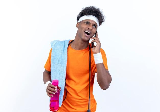 Il giovane sportivo afroamericano scontento che indossa la fascia e il braccialetto parla al telefono tenendo una bottiglia d'acqua con un asciugamano e la corda per saltare sulla spalla