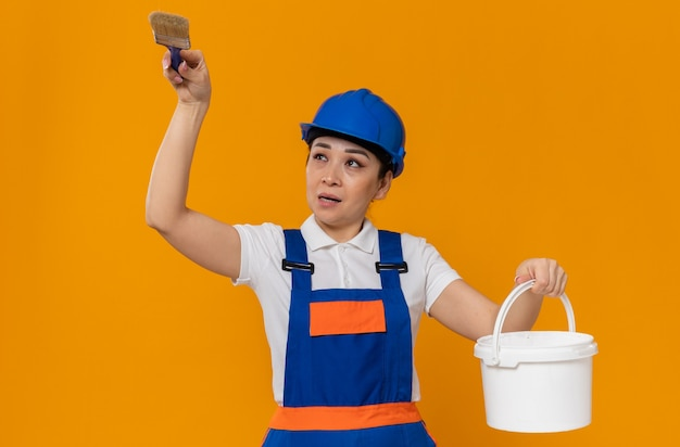 Giovane ragazza asiatica scontenta del costruttore con il casco di sicurezza blu che tiene il pennello e la pittura ad olio
