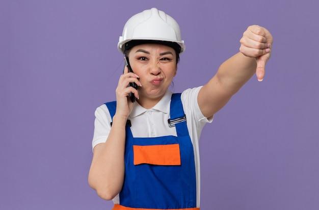 電話で話し、親指を下に白い安全ヘルメットを持つ不機嫌な若いアジアのビルダーの女の子