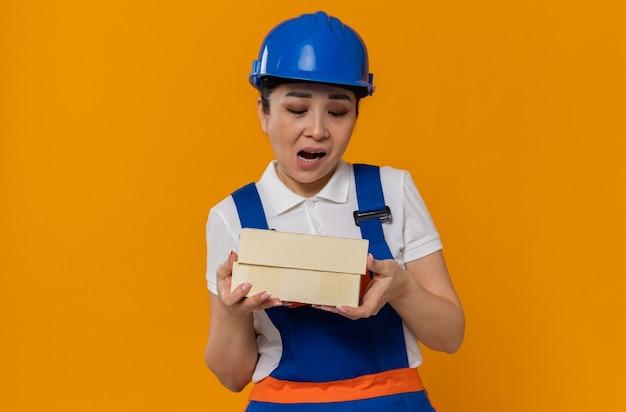 Giovane donna asiatica scontenta del costruttore con il casco di sicurezza blu che tiene e che guarda i mattoni