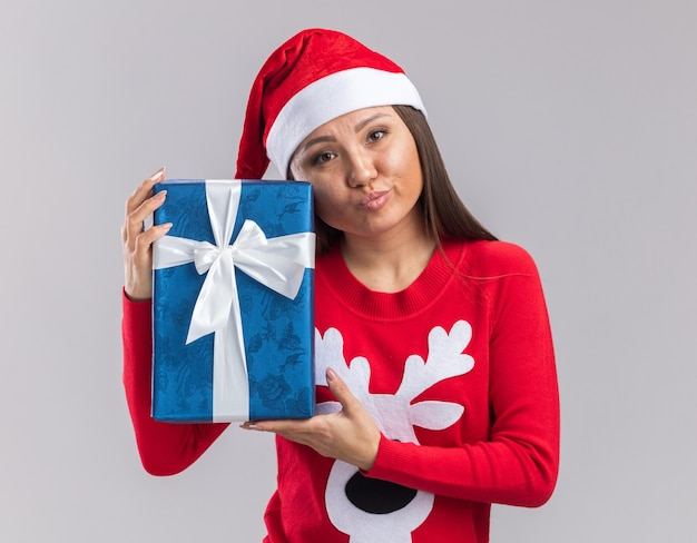 Недовольная молодая азиатская девушка в новогодней шапке со свитером, держащая подарочную коробку на белом фоне