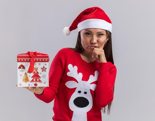 白い背景で隔離のあごの下に手を置くギフトボックスを保持しているセーターとクリスマス帽子をかぶって不機嫌な若いアジアの女の子