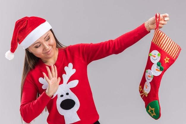 Una giovane ragazza asiatica scontenta che indossa un cappello di natale con un maglione che tiene e guarda il calzino di natale isolato su sfondo bianco