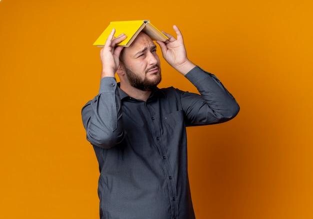 Недовольный молодой лысый человек колл-центра держит книгу на голове, глядя вверх с одним закрытым глазом, изолированным на оранжевом фоне с копией пространства