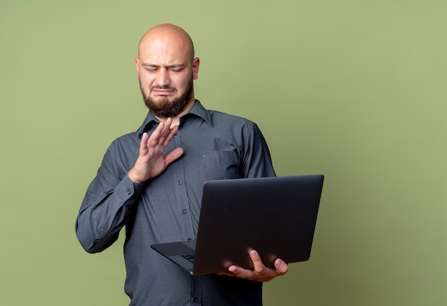 Uomo calvo giovane sgradevole della call center che tiene e che esamina il computer portatile e che non fa alcun gesto isolato su fondo verde oliva con lo spazio della copia
