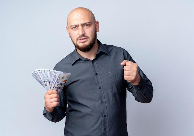 Soddisfatto giovane uomo calvo della call center che tiene i soldi e il pugno di serraggio isolato su priorità bassa bianca