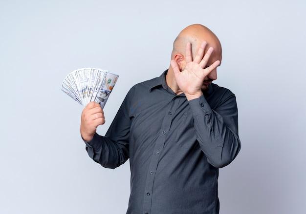 Soddisfatto giovane uomo calvo call center che tiene i soldi e nascondendo il viso dietro la mano isolato su sfondo bianco