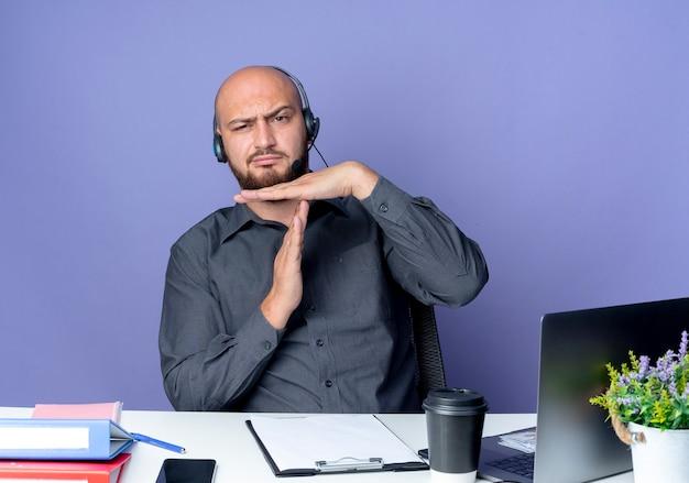 Soddisfatto giovane calvo call center uomo che indossa la cuffia avricolare seduto alla scrivania con strumenti di lavoro facendo gesto di timeout isolato su sfondo viola