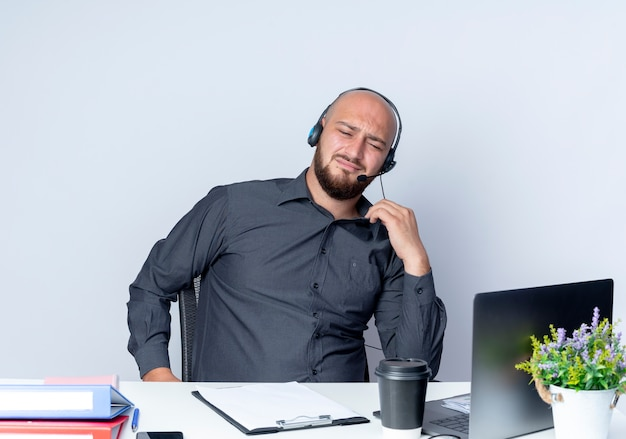 Unpleased young bald call center man wearing headset sitting at desk with work tools holding his collar looking down isolated on white background
