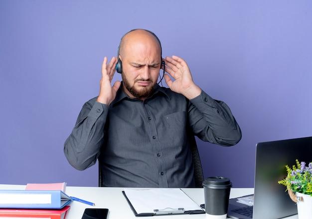 Soddisfatto giovane calvo call center uomo che indossa la cuffia avricolare seduto alla scrivania con strumenti di lavoro guardando verso il basso con le mani su auricolare isolato su sfondo viola