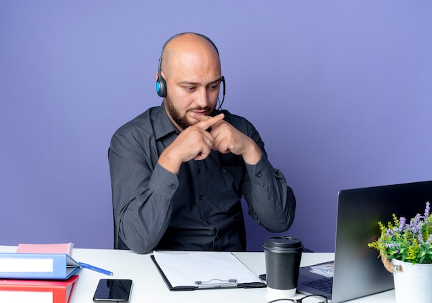 Unpleased young bald call center man wearing headset sitting at desk with work tools looking at laptop and gesturing no isolated on purple background