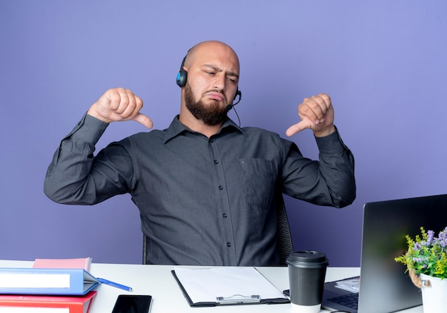 Soddisfatto giovane calvo call center uomo che indossa la cuffia seduto alla scrivania con strumenti di lavoro guardando il laptop e mostrando il pollice verso il basso isolato su sfondo viola
