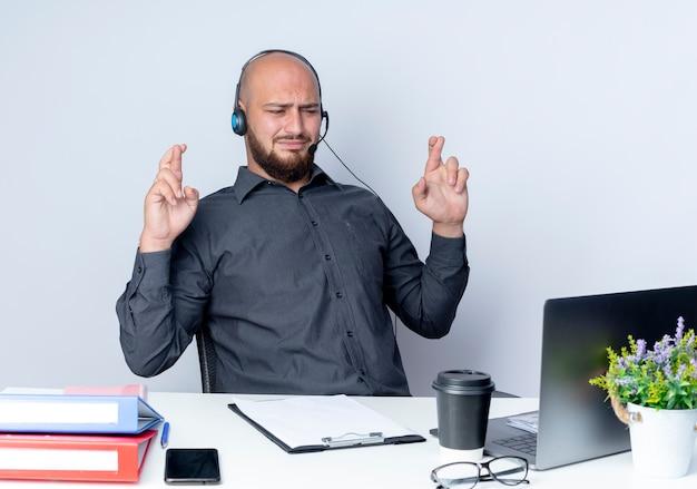 Soddisfatto giovane calvo call center uomo che indossa auricolare seduto alla scrivania con strumenti di lavoro guardando il computer portatile con le dita incrociate isolato su sfondo bianco