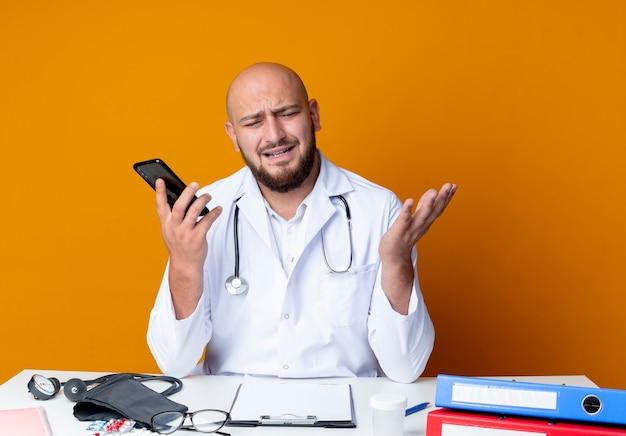의료 가운과 청진기를 착용하고 의료 도구가 전화를 들고 오렌지 배경에 고립 된 손을 확산과 작업 책상에 앉아 불쾌한 젊은 대머리 남성 의사