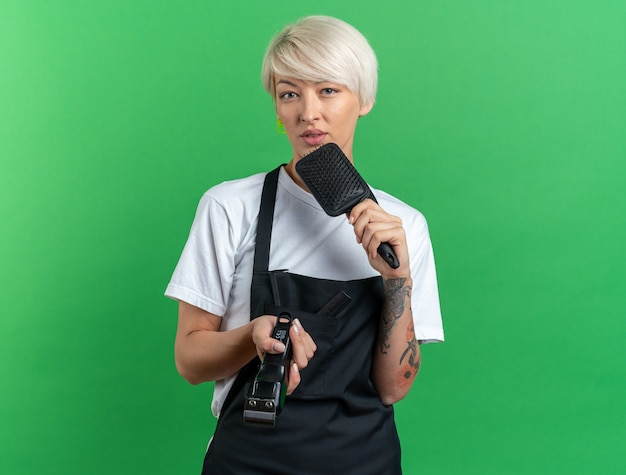 Unpleased young beautiful female barber in uniform holding hair clipper with comb isolated on green background