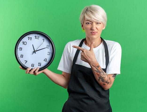 Giovane e bella barbiere scontenta in tenuta uniforme e punta all'orologio da parete isolato su sfondo verde