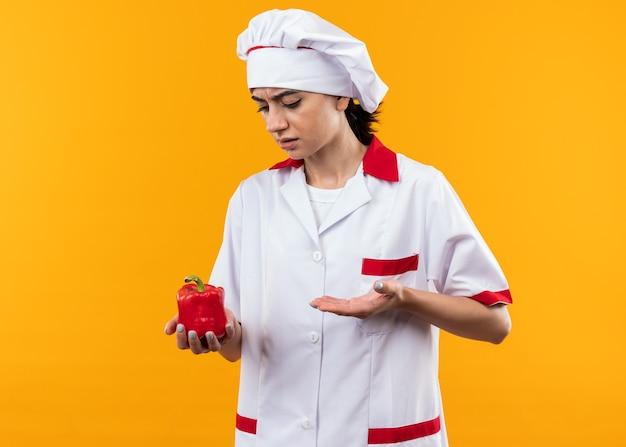Giovane bella ragazza scontenta in uniforme da chef che tiene e punta con la mano al pepe