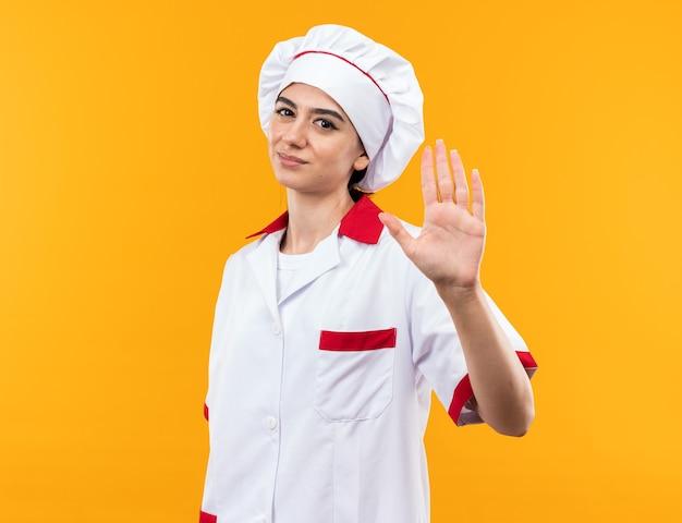 Giovane bella ragazza scontenta in uniforme da chef che mostra il gesto di arresto