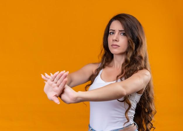 Недовольная молодая красивая девушка жестикулирует протянутыми руками на изолированной оранжевой стене
