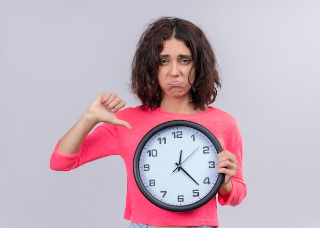 Unpleased young beautiful girl holding clock and showing thumb down on isolated white background with copy space