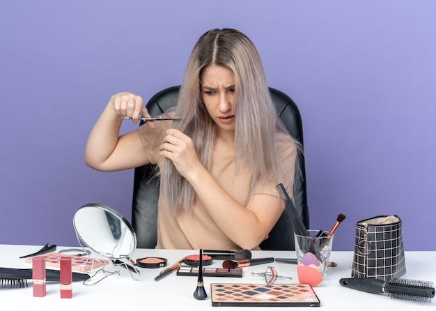 Unpleased young beautiful girl sits at table with makeup tools cutting hair with scissors isolated on blue background