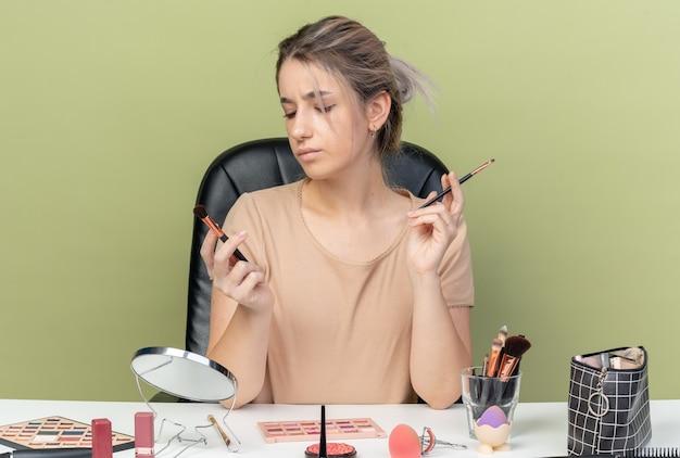 Giovane bella ragazza scontenta seduta alla scrivania con strumenti per il trucco che tengono e guardano i pennelli per il trucco isolati su sfondo verde oliva