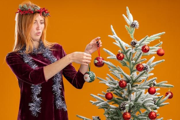 オレンジ色の壁にクリスマス ボールを保持している首にガーランドと赤いドレスと花輪を着てクリスマス ツリーの近くに立っている不愉快な美しい少女