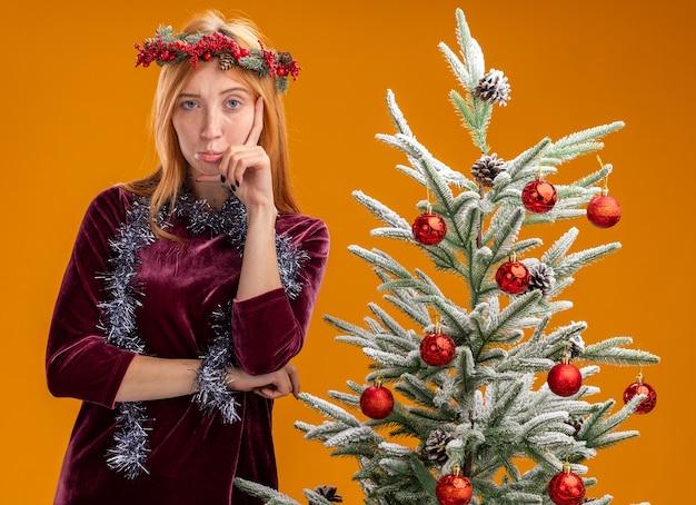 オレンジ色の壁に隔離された頬に手を置き、赤いドレスと花輪を首に付けた花輪を着てクリスマス ツリーの近くに立っている不愉快な美しい少女