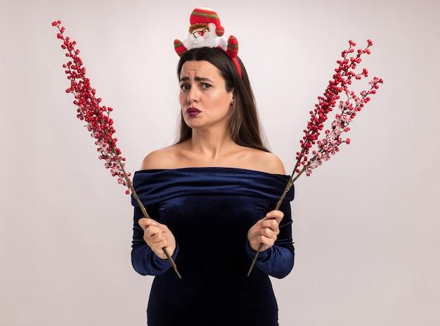 Недовольная молодая красивая девушка в синем платье и рождественском обруче для волос держит ветку рябины на белом фоне